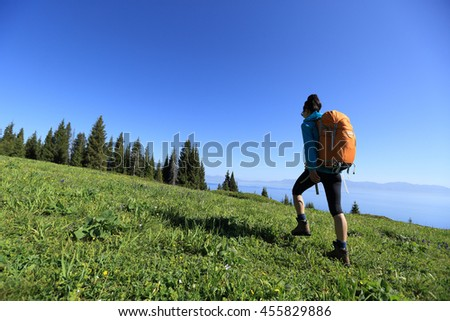 young woman backpacker hiking on sunrise mountain peak