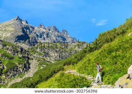 Young woman backpacker on hiking trail in summer landscape of High Tatra Mountains, Slovakia