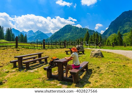 Young woman backpacker sitting at wooden picnic table in High Tatra Mountains in summer, Slovakia