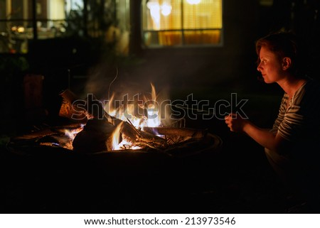 Young woman bakes apple on bonfire at night - stock photo