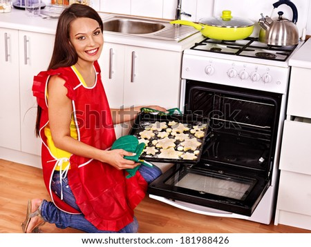 Young woman  baking cookies in oven.