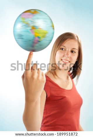 Young woman balancing a globe on her finger.