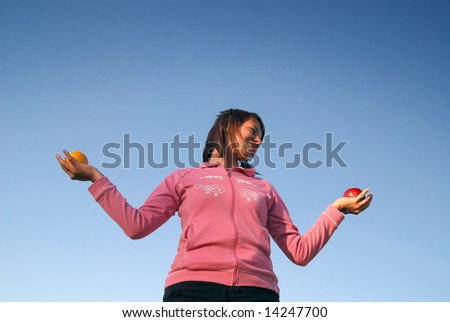 young woman balancing fruits in nature (healthy food and low calorie food concept)