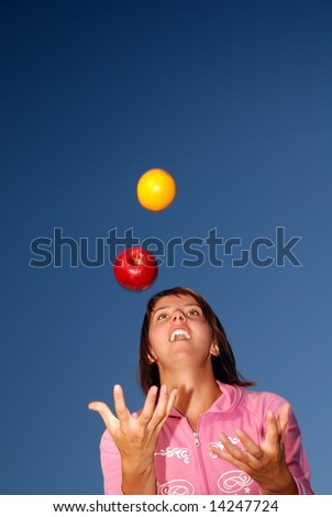 young woman balancing fruits in nature (healthy food and low calorie food concept) - stock photo