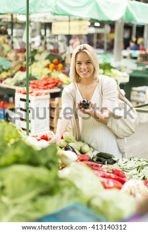 Young woman baying vegetable on the market