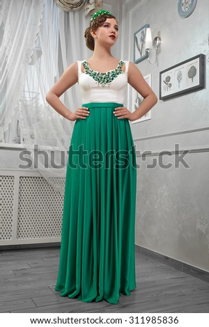 young woman, beautiful brunette in a long green dress, hands on hips; in the room - stock photo
