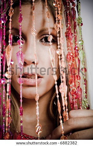 young woman behind candid curtain, studio shot - stock photo