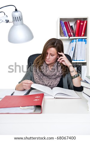 Young woman behind her desk studying diligently - stock photo