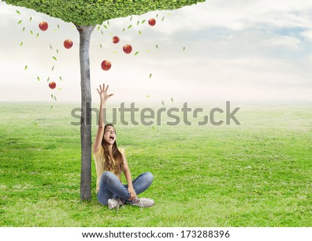 young woman being surprised by a red apple under a tree - stock photo