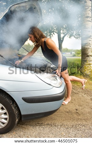 Young woman bending over the blown engine of her car, looking at the oil, whilst smoke is coming from under the hood - stock photo