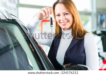 Young woman beside a new car in car dealership, obviously she is buying the auto, or making a test drive and holding the keys in hand