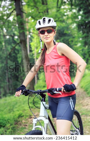young woman biking in a forest - stock photo