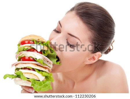 young woman biting a big sandwich, isolated on white background