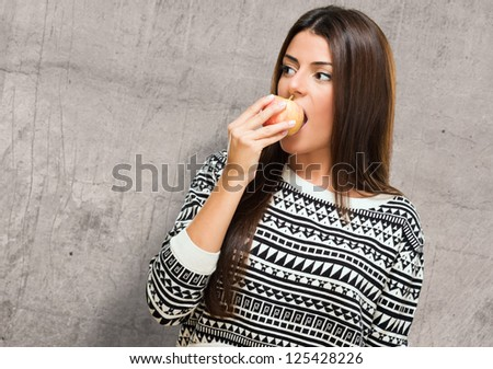 Young Woman Biting an Apple against a grunge background - stock photo