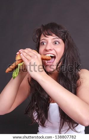 Young woman biting into a pleasurable Schnitzels / delicious schnitzel - stock photo