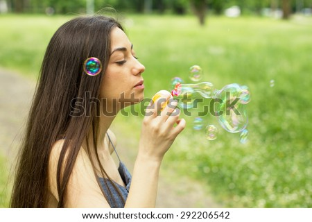 Young Woman Blowing Bubbles outdoor. Caucasian female Relaxing lifestyle in the park. - stock photo