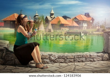 Young woman blowing bubbles whilst sitting next to water.