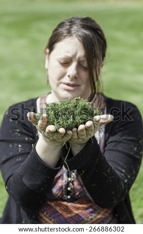 Young woman blowing grass, detail of young girl in nature, freedom - stock photo