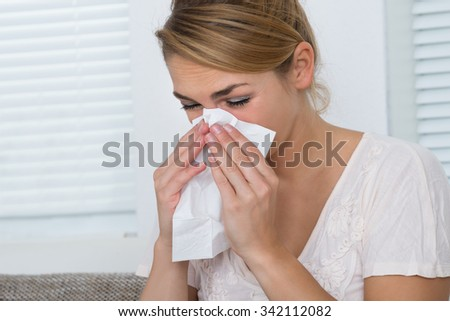 Young woman blowing nose while suffering from cold at home