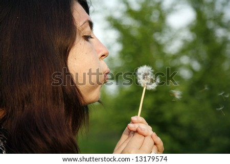 young woman blowing on dandelion