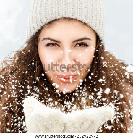 Young woman blowing snowflakes from hands