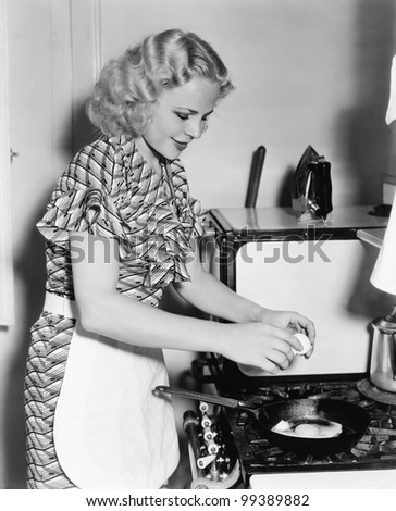Young woman breaking an egg into a frying pan - stock photo