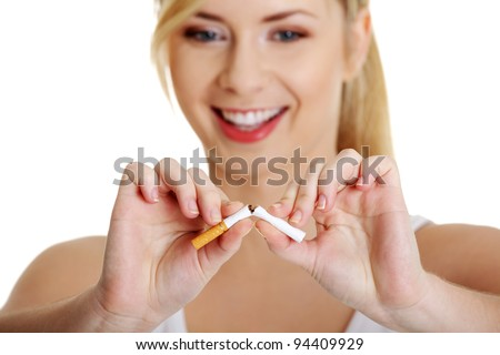Young woman breaking cigarette over white background - stock photo