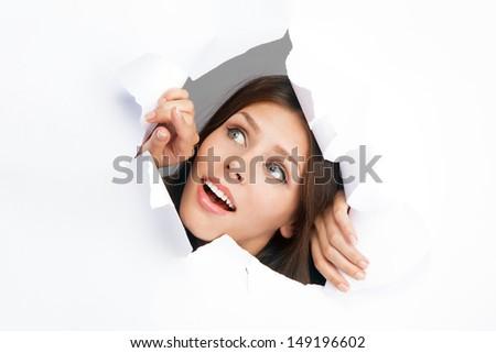 Young woman breaking through a paper sheet - stock photo