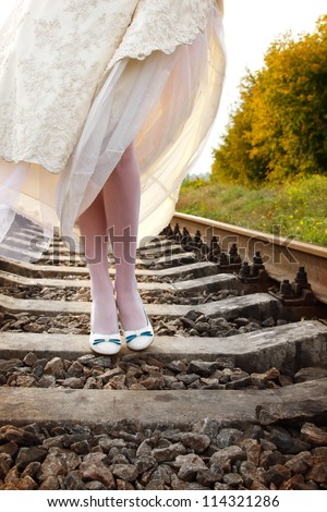 young woman bride's walks on the railway, summer nature outdoor, legs closeup - stock photo