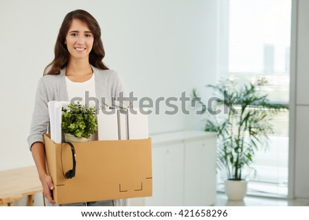 Young woman bringing her things to new workplace - stock photo