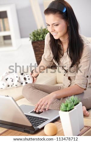 Young woman browsing internet on computer, sitting on sofa at home. - stock photo