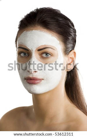young woman brunette with during a treatment with a beauty mask on her face