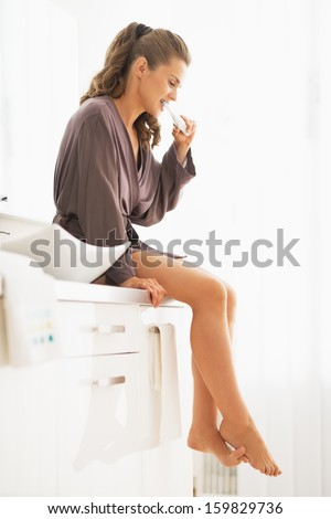 Young woman brushing teeth while sitting in bathroom