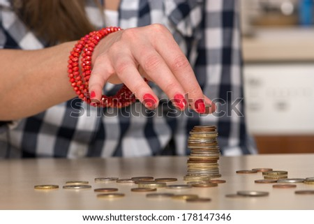 Young woman building coin-stacks - stock photo