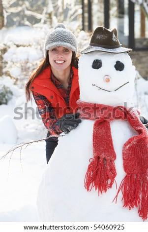 Young Woman Building Snowman In Garden - stock photo