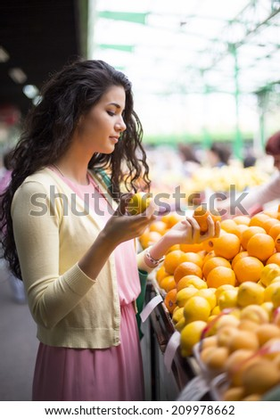 Young woman buying fruits at the market - stock photo