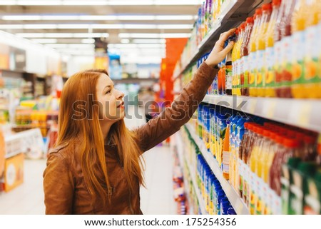 Young woman buying juice in the supermarket - stock photo