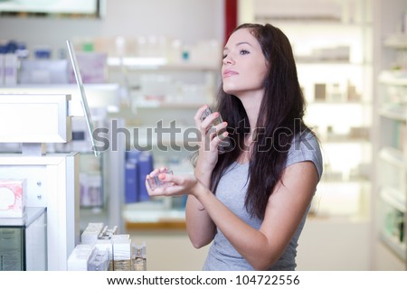 Young woman buying perfume in a beauty store - stock photo