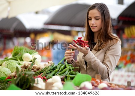 Young woman buying red hot chili peppers at the market - stock photo