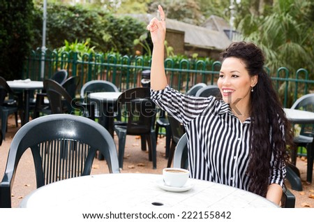 young woman calling the waiter.