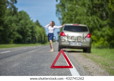 Young woman calling to car assistance after breakdown on the road.Closeup of Red triangle warning sign.