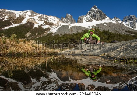 Young woman camps in high mountains, Patagonia, Chile, South America - stock photo
