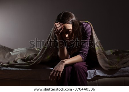 Young woman can not sleep. She is sitting on her bed and thinking. - stock photo