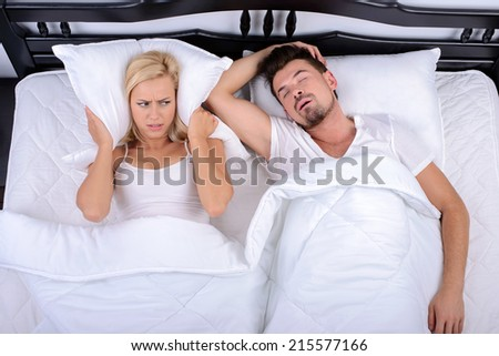 Young woman can not sleep through the snoring of her husband in her bedroom - stock photo