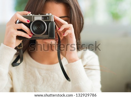 Young Woman Capturing Photo, Indoors - stock photo