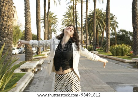 Young woman carelessly walking in town with her arms outstretched in the air, feeling happy. - stock photo