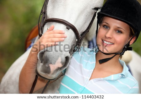 Young woman caressing her horse - stock photo