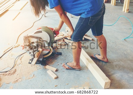 Young woman carpenter using electric circular saw cutting piece of wood in sawmill
