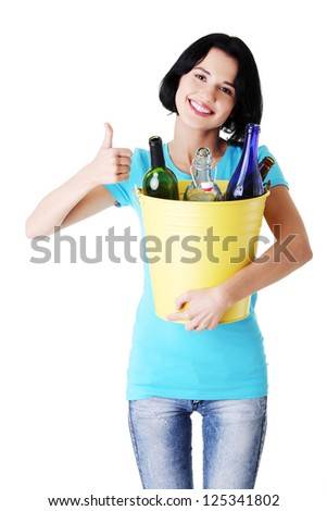 Young woman carrying a bin full of empty recyclable glass bottles. Recycling concept - stock photo