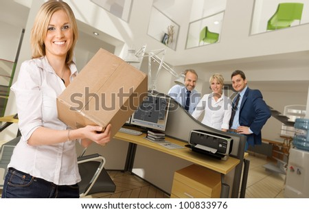 Young woman carrying a box in a beautiful office interior - stock photo